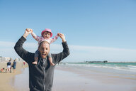 France, La Baule, portrait of father carrying his little daughter on shoulders on the beach - GEMF02032