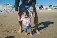 France, La Baule, baby girl learning to walk with her father on the beach - GEMF02038