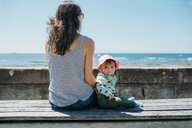 France, mother and baby girl sitting on a bench at beach promenade - GEMF02044