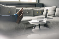 Businessman's feet on couch next to laptop - JOSF02191