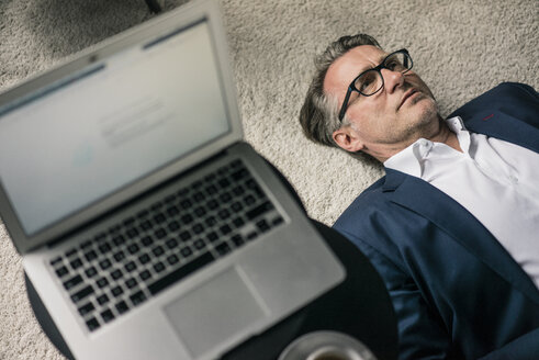 Mature businessman lying on carpet next to laptop - JOSF02197