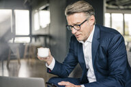 Mature businessman with cup of coffee and laptop using cell phone - JOSF02200
