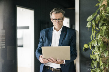 Mature businessman standing in office using laptop - JOSF02206
