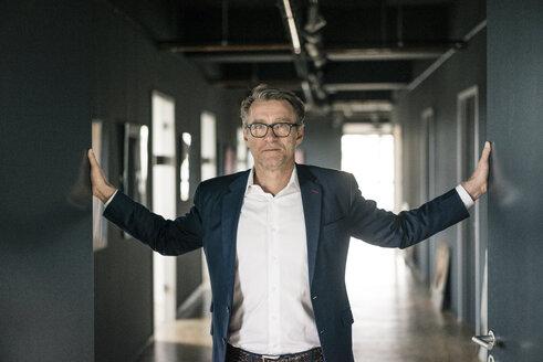 Portrait of mature businessman standing on office floor - JOSF02209