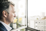 Serious mature businessman looking out of window - JOSF02218