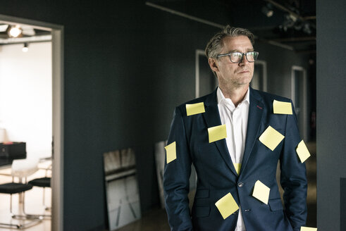Serious mature businessman covered with sticky notes looking sideways - JOSF02221