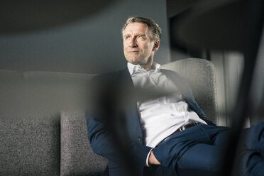 Mature businessman sitting on couch looking sideways - JOSF02233