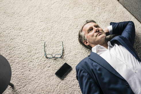 Mature businessman lying on carpet next to cell phone - JOSF02236