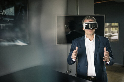 Mature businessman wearing VR glasses in office - JOSF02239