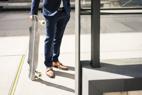 Businessman holding longboard outdoors - JOSF02245