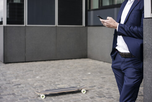 Businessman with longboardusing cell phone outdoors - JOSF02257