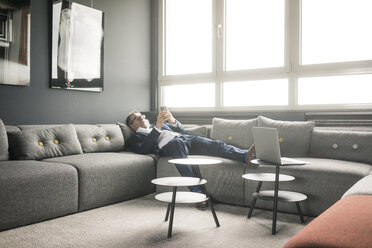 Mature businessman lying on couch using cell phone - JOSF02260