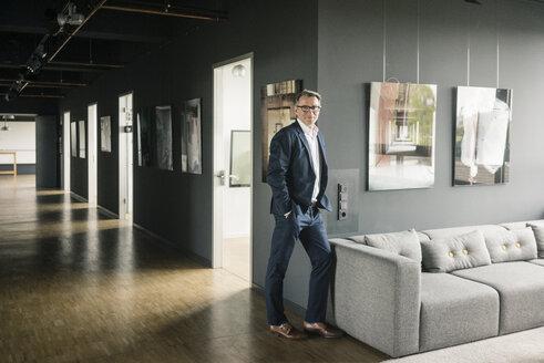 Portrait of confident mature businessman standing on office floor - JOSF02266