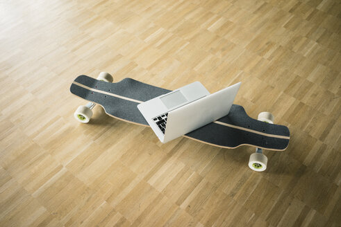 Laptop and longboard on wooden floor - JOSF02272