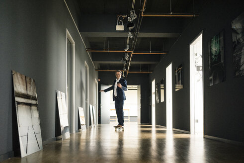Businessman riding longboard and using cell phone on office floor - JOSF02275