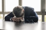 Mature businessman resting his head on the table - JOSF02281