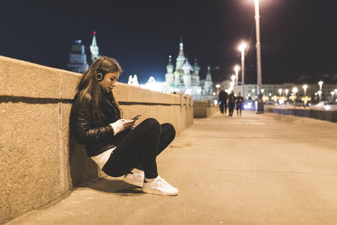 Russia, Moscow, beautiful woman listening music in the city at night - WPEF00351