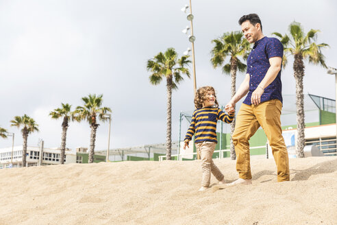 Spain, Barcelona, father and son walking hand in hand on the beach - WPEF00354