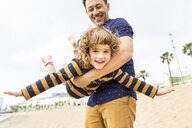 Spain, Barcelona, father and son playing on the beach - WPEF00357