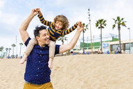 Spain, Barcelona, father with son on the beach giving a piggyback ride - WPEF00360