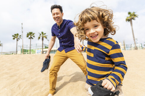 Spain, Barcelona, father and son playing on the beach - WPEF00372