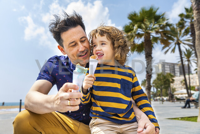 Spain, Barcelona, father and son enjoying an ice cream at seaside - WPEF00381 - William Perugini/Westend61