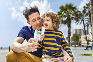 Spain, Barcelona, father and son enjoying an ice cream at seaside - WPEF00381