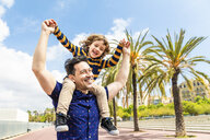 Spain, Barcelona, happy father carrying son on shoulders - WPEF00384