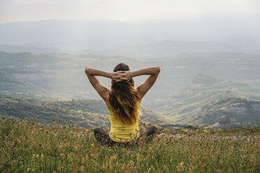 Spain, Barcelona, back view of young woman relaxing on Montcau Mountain - AFVF00541