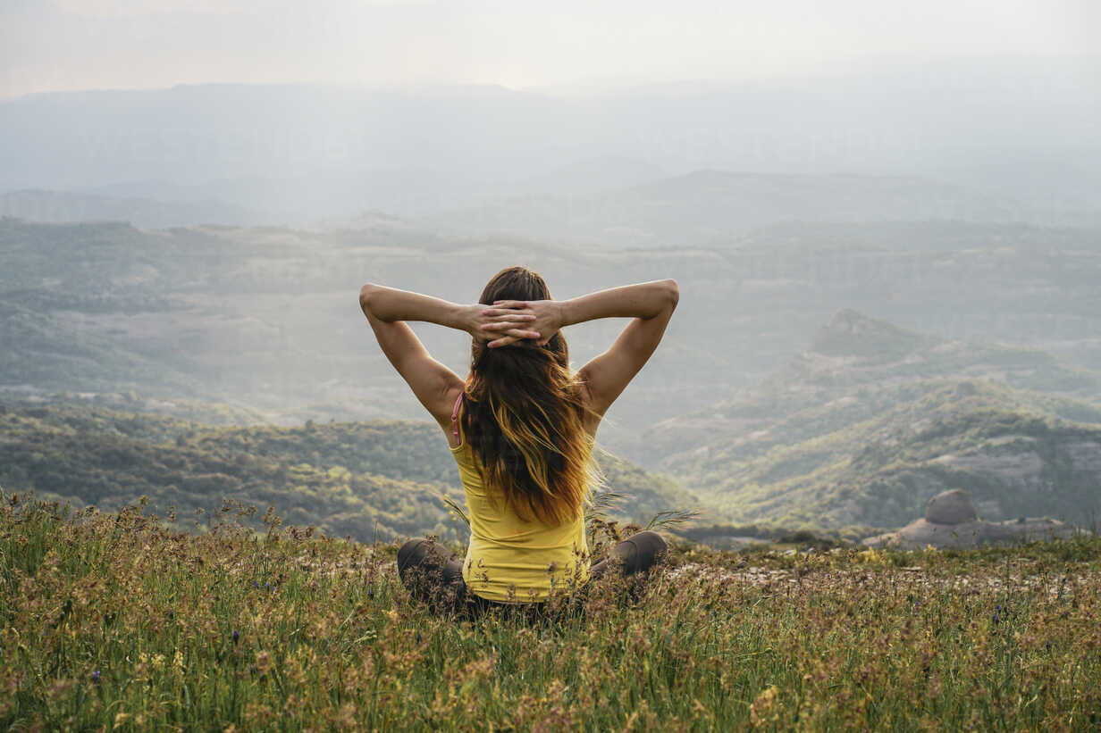 Spain, Barcelona, back view of young woman relaxing on Montcau Mountain - AFVF00541 - VITTA GALLERY/Westend61