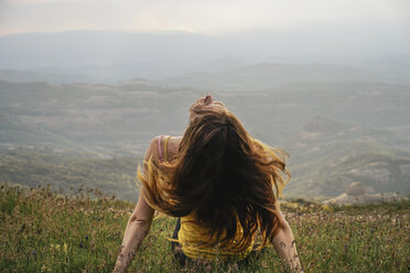 Spain, Barcelona, back view of young woman sitting on meadow tossing her hair - AFVF00544