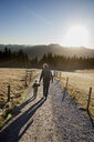 Rear view of man and toddler daughter walking on dirt track, Tegernsee, Bavaria, Germany - CUF15117
