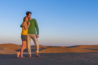 Romantic mid adult couple on sand dunes watching sunset, Maspalomas, Gran Canaria, Canary Islands, Spain - CUF15123