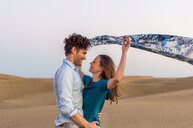 Mid adult couple holding up blowing scarf on dunes, Maspalomas, Gran Canaria, Canary Islands, Spain - CUF15126