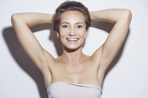 Young woman wearing tube top, hands behind head looking at camera smiling - CUF15180