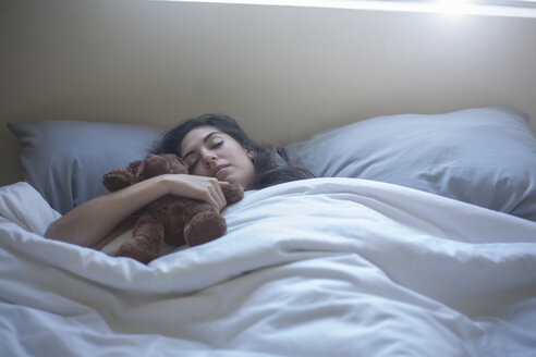 Young woman with teddy bear, sleeping in bed - CUF15243