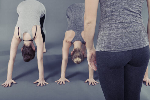 Young women practising yoga, grey background - CUF15285