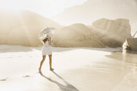 Rear view of woman strolling with parasol on sunlit beach, Cape Town, South Africa - CUF15303