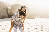 Man giving girlfriend a piggy back on sunlit beach, Cape Town, South Africa - CUF15306