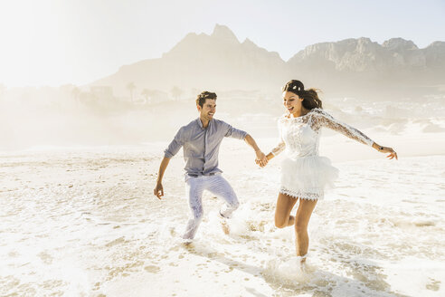 Couple running and splashing in sunlit sea, Cape Town, South Africa - CUF15309