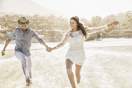 Couple running and splashing in sea, Cape Town, South Africa - CUF15318