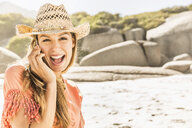 Portrait of woman wearing straw hat talking on smartphone at beach, Cape Town, South Africa - CUF15330