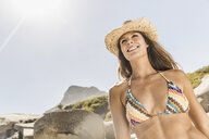 Low angle view of woman wearing bikini top and straw hat on beach, Cape Town, South Africa - CUF15339