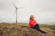 Runner taking break on wind farm, Eysturoy, Faroe Islands - CUF15360