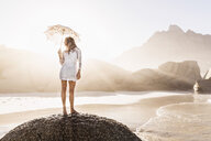 Woman standing on rock with parasol on sunlit beach, Cape Town, South Africa - CUF15366