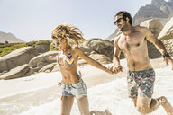 Couple wearing swimwear running on beach, Cape Town, South Africa - CUF15378