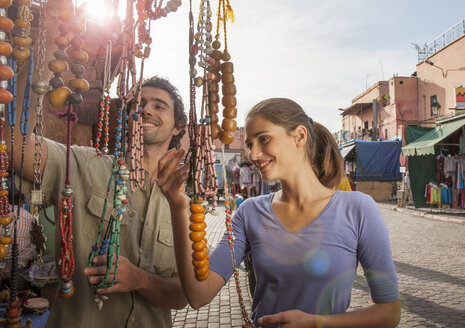 Young couple at market looking at beads, Jemaa el-Fnaa Square, Marrakesh, Morocco - CUF15381