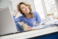 Happy woman sitting at kitchen table with laptop - CUF15399