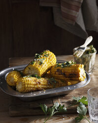 Bistro table with dish of corn on the cob and herb butter - CUF15576