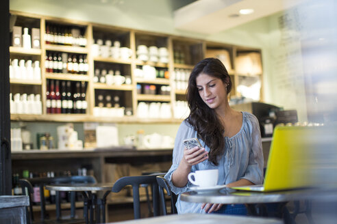 Young woman reading smartphone texts in cafe - CUF15846